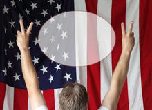 Peace American Style. A man displays the peace sign toward the American flag royalty free stock photos