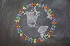 Peace Around the World. A hand drawn chalkboard shows multi-ratial people holding hands around the world to show care for the earth, peace, and unity