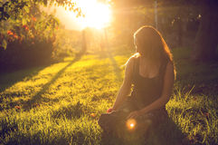Peace in the backyard. Young woman in the backyard with a beautiful sunlight in the background Royalty Free Stock Images