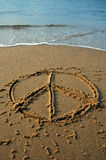Peace beach. Peace sign written in sand on a beach, cyan water in background royalty free stock photos