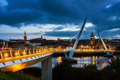 Peace bridge in Derry Londonderry in Northern Ireland with city center. Derry, Ireland. Illuminated Peace bridge in Derry Londonderry in Northern Ireland with stock photo