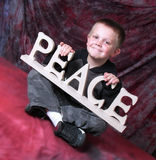 Peace child. A little boy holding a peace sign and smiling Stock Photos