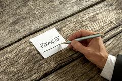Peace concept written on a memo. By a businessman seated at a rustic wooden table, close up of his hand and the handwritten note Royalty Free Stock Photo