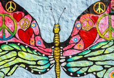Peace concepts painted over butterfly painting on grunge wall. Peace symbol,heart shape and other different peace concepts painted over butterfly painting on stock photos