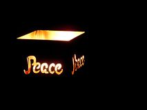 Peace cutout illuminated in candle holder. Royalty Free Stock Photography