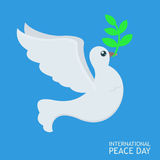 White Peace dove with olive branch for International Peace Day poster on blue sky abckground Stock Photo
