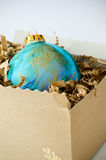Peace on Earth. Peace written in gold on blue green ornament resembling the earth.  It is nestled in packing material in a cardboard box Royalty Free Stock Photos