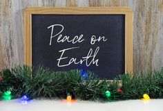 Peace on earth message on black chalkboard. With Christmas lights and green garland Stock Photo