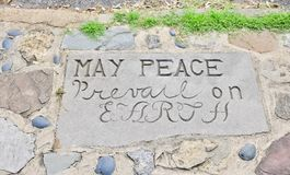 Peace on Earth. A stone tablet in the ground ask that peace prevail on earth Royalty Free Stock Images