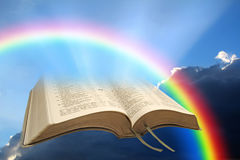 Peace of god rainbow bible. Concept photo of peace from god showing open bible with rainbow against storm clouds Royalty Free Stock Images