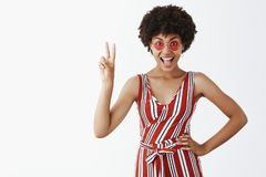 Peace guys let us shake party. Portrait of joyful self-assured emotive and stylish african american woman in trendy. Sunglasses and striped overalls showing royalty free stock photos