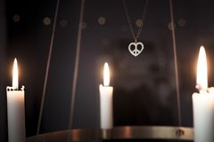 Peace heart symbol necklace and candles glowing on advent chandelier royalty free stock photography