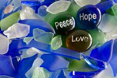 Peace, Hope, and Love on Glass Stones. Inspiration messages of peace, hope, and love on glass stones with sea glass stock photography