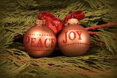 Peace and joy. Gold Christmas  tree decorations on cedar branches Royalty Free Stock Images