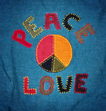 Peace and love. A piece of fabric with Peace and Love and a peace sign sewn into the surface Stock Photo