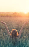 Peace and love, hipster woman celebrates the birth of the sun in a wheat field Stock Photography