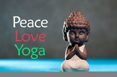 Peace love yoga - concept of freedom and happiness. figurine of babby buddha or little prayer practicing yoga or Stock Photos