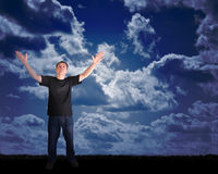 Peace Man Reaching to the Sky with Hope. A man is wearing a black t-shirt and is standing on grass outdoors and reaching for the sky. There are dark blue clouds stock images