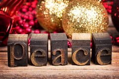 Peace message. The word PEACE written with vintage wood printer blocks. Christmas message over old wood with traditional tree decorations behind royalty free stock photos
