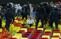 Peace in the middle of the storm. Senior football fan sit peaceful on his seat during a fight between constabulary forces and ultras supporters