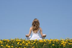 Peace of mind. Longhaired young woman in white clothes relaxing in a flowering dandelion field Stock Images