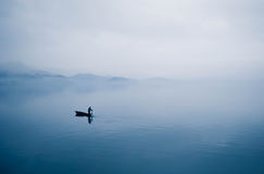 Peace of Mind. The boat slided into lake,  and fisherman's songs dissolved in fog Royalty Free Stock Photo