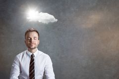 Peace of mind. Man in a white shirt and necktie with a light smile. Above his head is a cloud with the sun emerging from behind Royalty Free Stock Photography