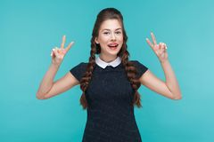 Peace, optimistic look! Happiness young woman showing v sign. Indoor, studio shot on blue background stock photo