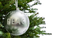 Peace ornament hanging from a Christmas tree branch Royalty Free Stock Photo