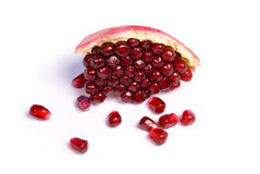 Peace of pomegranate with scatter seeds. On white background Royalty Free Stock Image