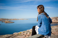 Peace by the sea. Young and happy tourist woman sitting in the harbour in Smogen town, Sweden Royalty Free Stock Photography