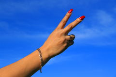 Peace Sign. Woman's hand showing peace sign over blue sky Royalty Free Stock Photography