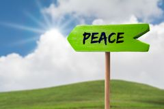 Peace sign arrow sign. Peace sign green wooden arrow sign on green land with clouds and sunshine stock photos