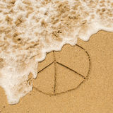 Peace sign drawn on the sand of a beach with the soft wave. Stock Image