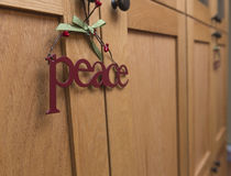 A metal piece sign hangs at home on christmas. A holiday peace sign on cabinets in a kitchen Stock Image