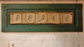 Peace. Sign mounted with green wood frame hanging on painted brick wall stock photos