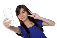 Peace sign selfie with phone. Beautiful Asian teenage girl take a selfie photo using front camera in her smartphone and make a peace sign with her hand, isolated Stock Photography