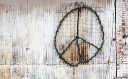 Peace Sign on the side of a building. Peace sign on the side of a white structure tagged with Christmas lights royalty free stock photography