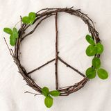Peace sign, symbol of natural material - flowers, leaves, wooden sticks on tissue white background.  Stock Photo