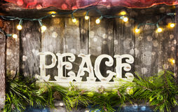 Peace sign on vintage wooden surface. A peace sign on a textured wooden base framed by yellow and white lights and pine branches. Christmas or New Years concept stock image