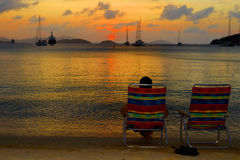Peace at Sunset. A man occupies one of two chairs on a beach and watches the sunset over a bay full of boats Stock Image