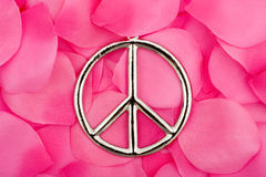 Peace Symbol. A peace symbol sitting on a pink flower petal background, peace symbol Royalty Free Stock Images