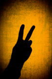 Peace Symbol. Shadow of a hand displaying the peace sign with gritty yellow background Stock Images