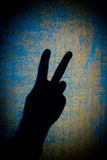 Peace Symbol. Shadow of a hand displaying the peace sign with gritty blue and yellow background Stock Photo