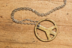 Peace symbol necklace. Rusty Peace symbol necklace on wooden surface Stock Photography