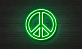 Peace symbol neon sign on brick wall background. Stock Images
