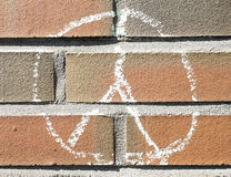 Peace. Symbol painted with chalk on a brick wall Royalty Free Stock Photos