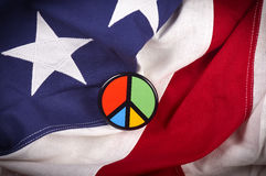 Peace symbol pin on American flag Stock Photos