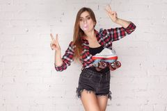 Peace! Trendy woman holding quads and showing v sign. Stock Photo