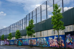 Peace wall. Belfast, Northern Ireland: This peace wall in Belfast, dividing the Falls and Shankill Roads, is one of a series of barriers that have been built in Stock Image